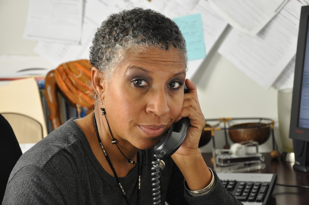 African American professional woman looking at you while on the telephone